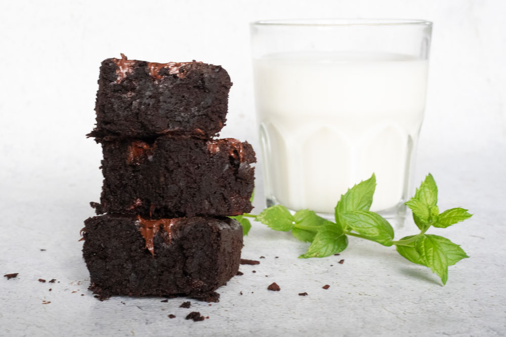 stack of three brownies with glass of milk